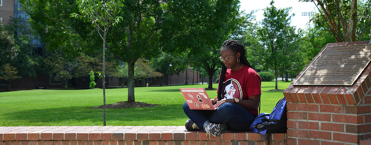 Girl in an FSU shirt, with a backpack and laptop, sitting on a brick wall with green grass and trees behind it.