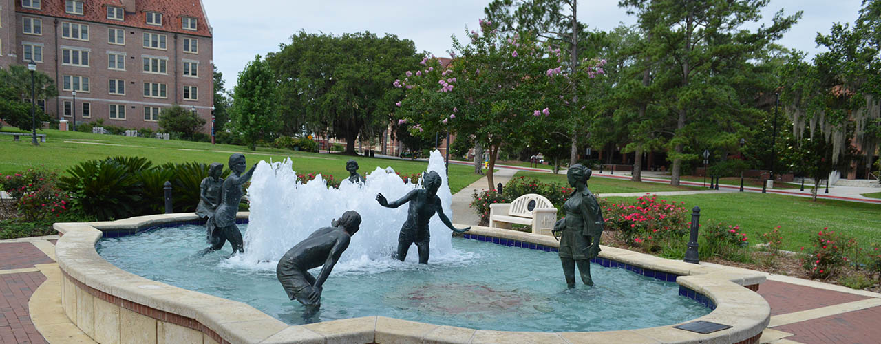 Fountain on campus with statues of people playing in the water.